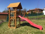 Kis játszótér rönkfából fa tetővel fészekhintával