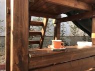 Kis torony fa tetővel, homokozóval fészekhintával és eladó pulttal